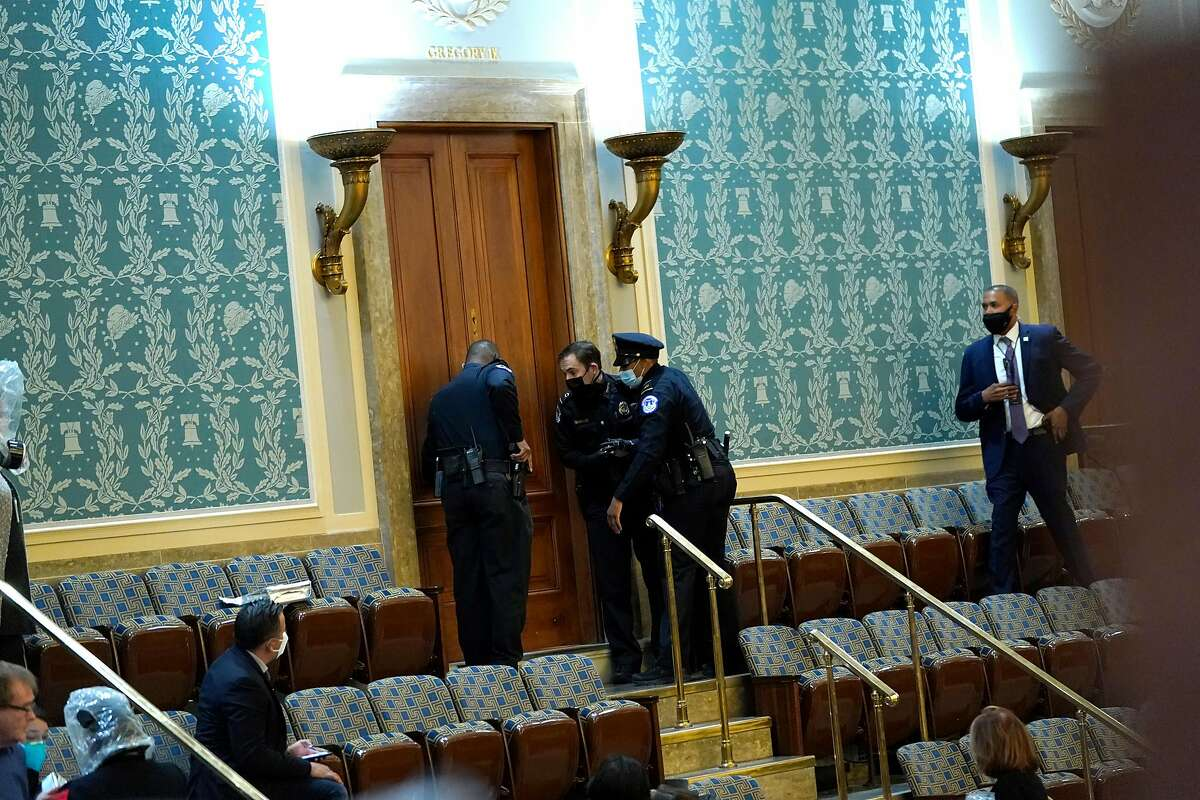 Capitol Police draw their guns as Trump supporters attempt to enter the House Chamber during a joint session of Congress on January 06, 2021 in Washington, DC.