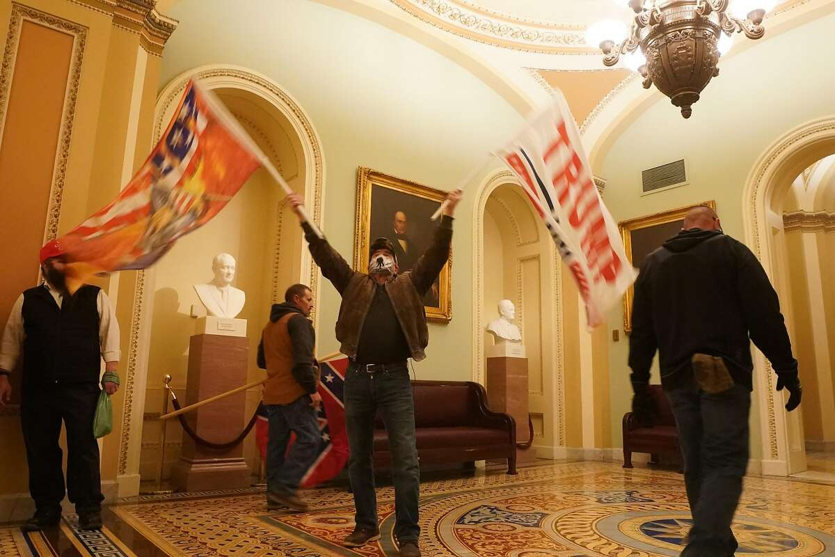 Trump supporters wave flags inside the Capitol in Washington on Wednesday, Jan. 6, 2021.