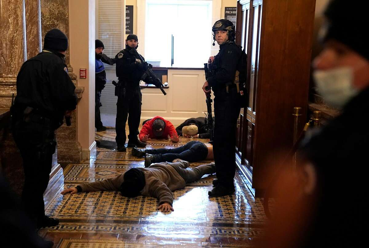 U.S. Capitol Police detain Trump supporters outside of the House Chamber during a joint session of Congress on January 06, 2021 in Washington, DC.