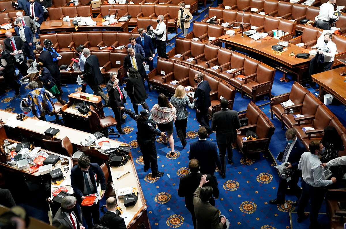 WASHINGTON, DC - JANUARY 06: Members of Congress evacuate the House Chamber as protesters attempt to enter during a joint session of Congress on January 06, 2021 in Washington, DC. Congress held a joint session today to ratify President-elect Joe Biden's 306-232 Electoral College win over President Donald Trump. A group of Republican senators said they would reject the Electoral College votes of several states unless Congress appointed a commission to audit the election results. Pro-Trump protesters entered the U.S. Capitol building after mass demonstrations in the nation's capital. (Photo by Drew Angerer/Getty Images)