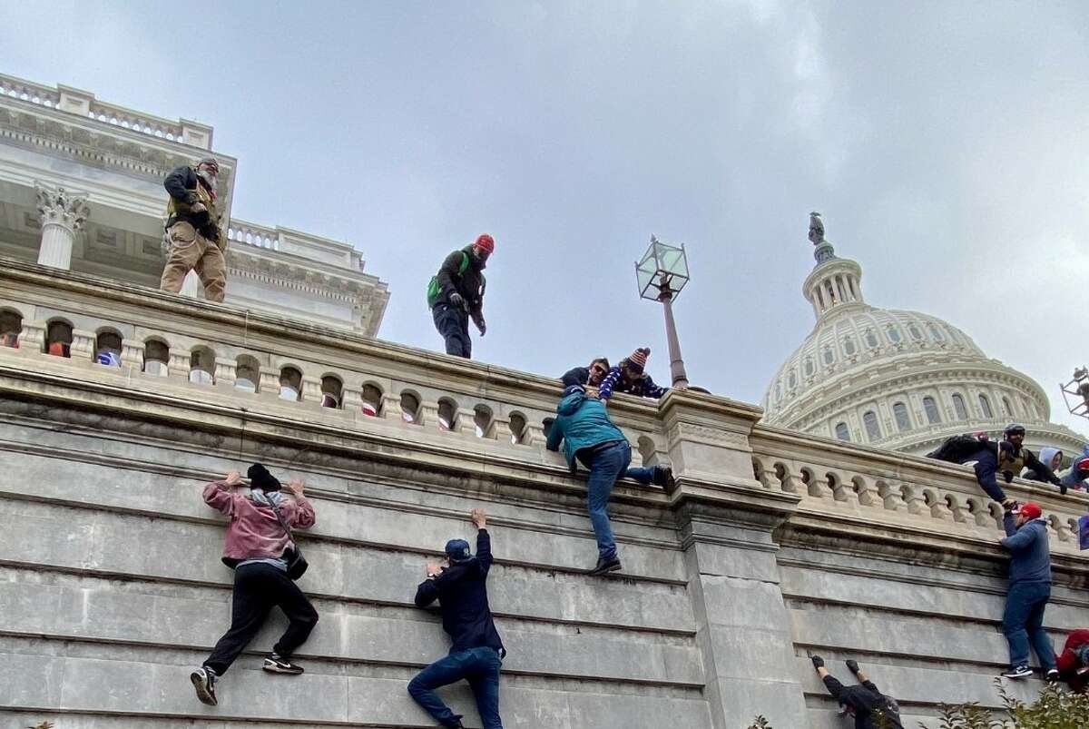 Trump supporters climb a wall outside the Capitol building in D.C. Wednesday as an insurrection unfolds over the counting of electoral votes in the 2020 presidential election.