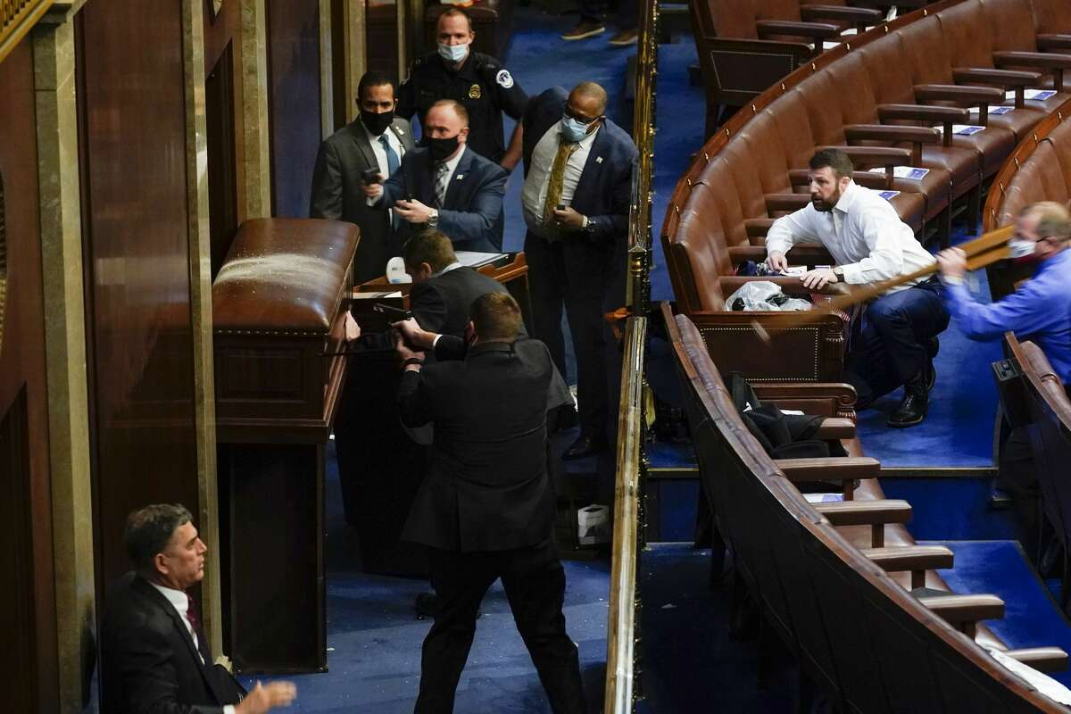U.S. Capitol Police with guns drawn stand near a barricaded door as protesters try to break into the House Chamber at the U.S. Capitol on Wednesday, Jan. 6, 2021, in Washington. Former Fort Bend County Sheriff Troy Nehls is there in the blue shirt. (AP Photo/Andrew Harnik)