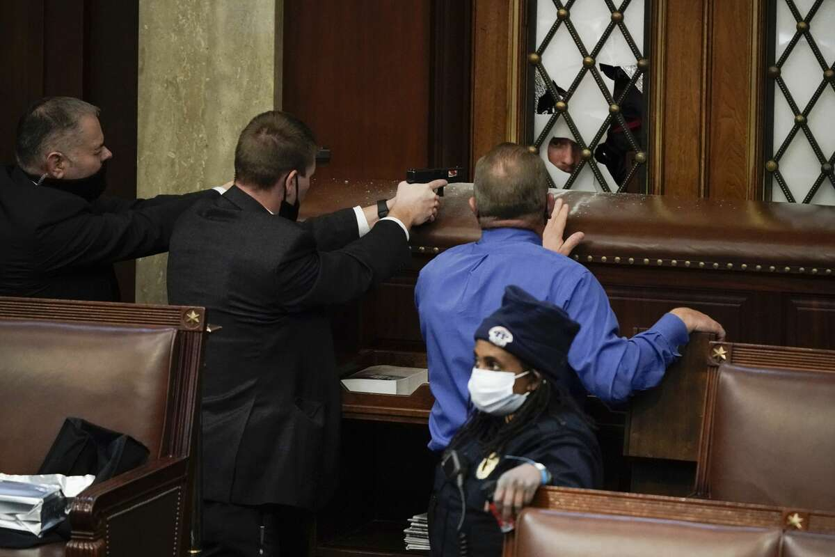 Police with guns drawn watch as protesters try to break into the House Chamber at the U.S. Capitol on Wednesday, Jan. 6, 2021, in Washington. Former Fort Bend County Sheriff Troy Nehls is there in the blue shirt. (AP Photo/J. Scott Applewhite)