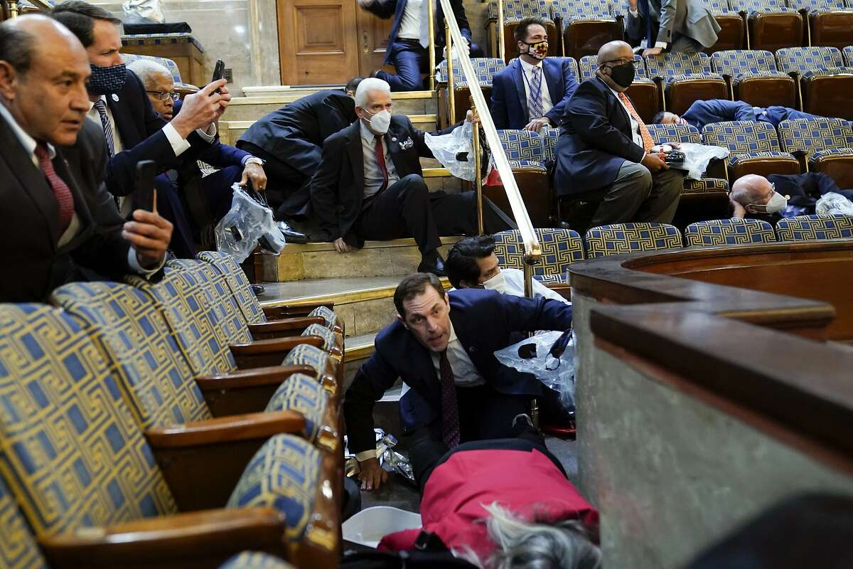 People shelter in the House gallery as Trump supporters try to break into the House Chamber at the U.S. Capitol on Wednesday, Jan. 6, 2021, in Washington.