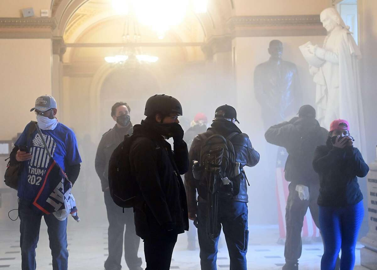 Supporters of President Donald Trump enter the US Capitol as tear gas fills the corridor on January 6, 2021, in Washington, DC.