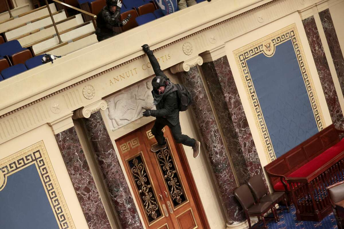 WASHINGTON, DC - JANUARY 06: A protester is seen hanging from the balcony in the Senate Chamber on January 06, 2021 in Washington, DC. Congress held a joint session today to ratify President-elect Joe Biden's 306-232 Electoral College win over President Donald Trump. Pro-Trump protesters have entered the U.S. Capitol building after mass demonstrations in the nation's capital. (Photo by Win McNamee/Getty Images)
