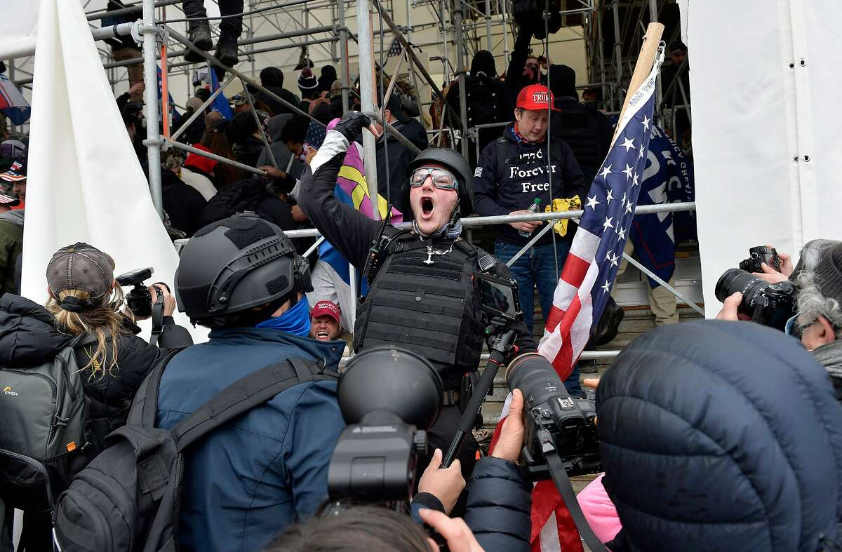 A man calls on people to raid the building as Trump supporters clash with police and security forces as they try to storm the Capitol Building in Washington D.C on January 6, 2021.