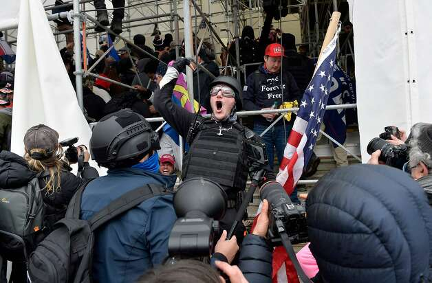A man calls on people to raid the building as Trump supporters clash with police and security forces as they try to storm the Capitol Building in Washington D.C on January 6, 2021. Photo: Joseph Prezioso, AFP Via Getty Images