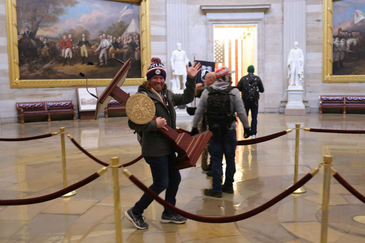 A member of a pro-Trump mob that entered the U.S. Capitol Building on January 06, 2021 in Washington, DC, stopped for a photo with Speaker of the House Nancy Pelosi's lecturn. Congress held a joint session today to ratify President-elect Joe Biden's 306-232 Electoral College win over President Donald Trump.