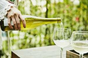 Woman pouring white wine into glasses.