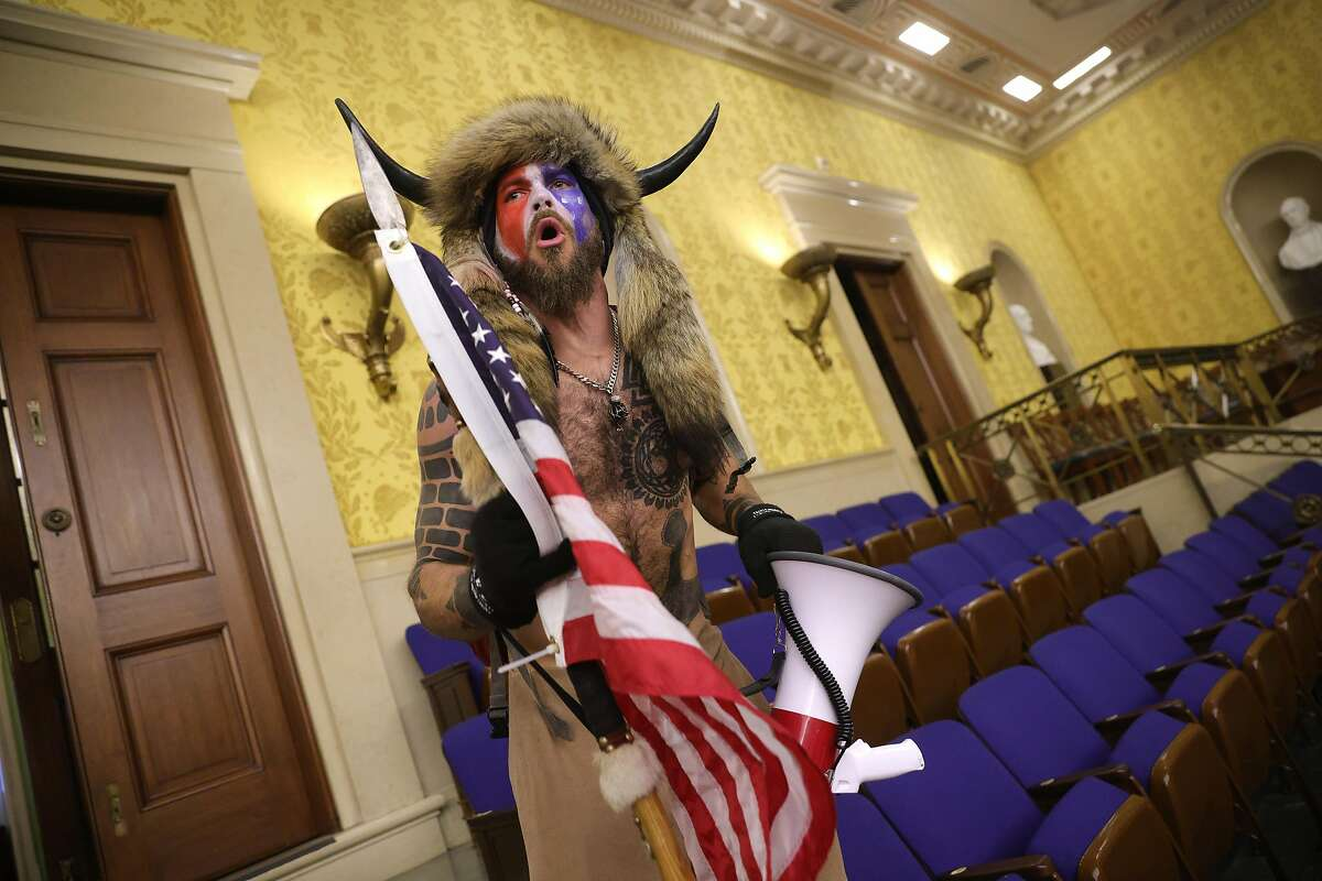 The Q Shaman shouts inside the Senate chamber after the U.S. Capitol was breached by a mob during a joint session of Congress on January 6.