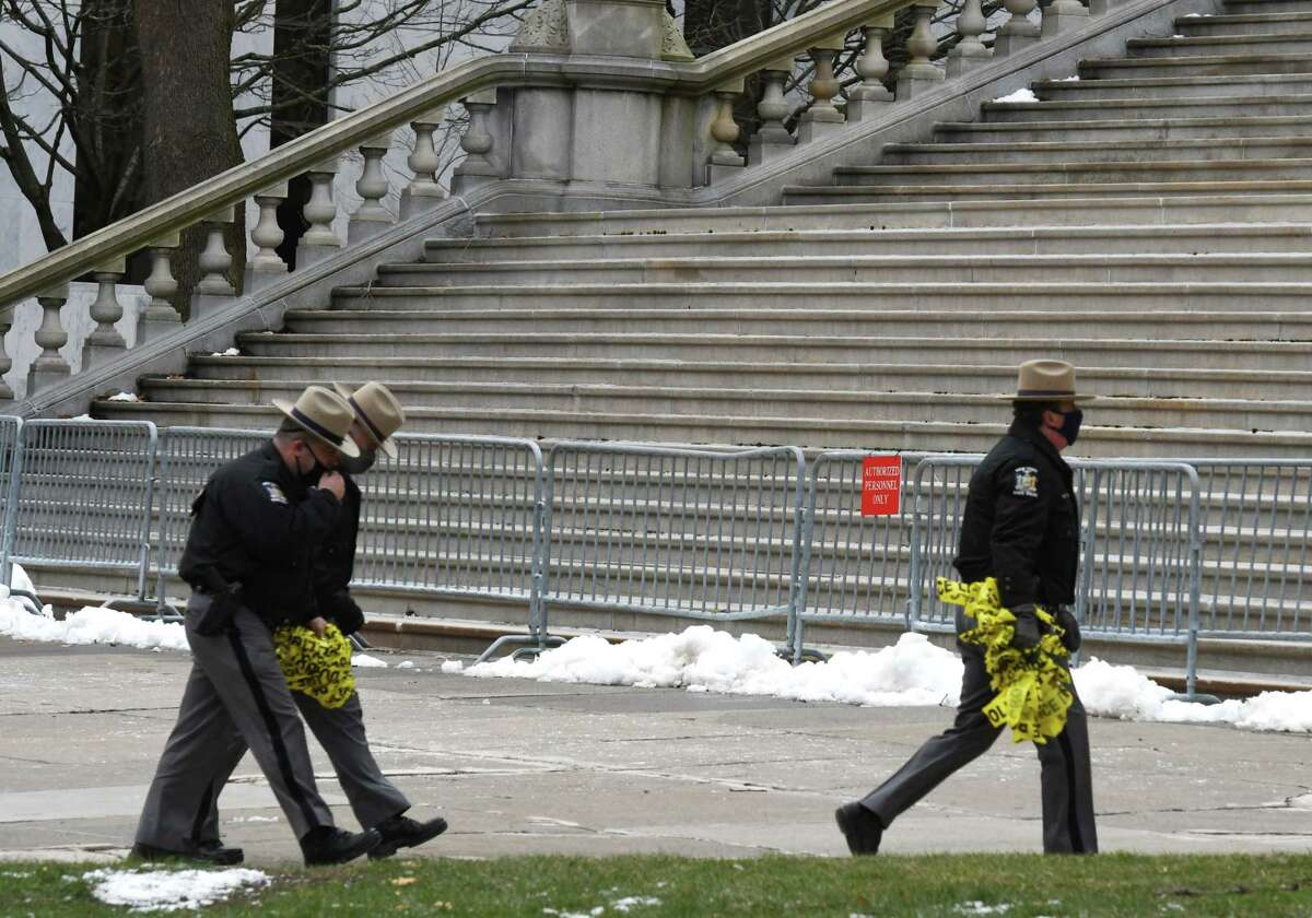 New York State Troopers clear crime tape from East Capitol Park following a stabbing which took place during a clash between protesters on Wednesday, Jan. 6, 2021, in Albany, N.Y. Police say two people were taken to Albany Medical Center Hospital for treatment and one person is in custody. (Will Waldron/Times Union)