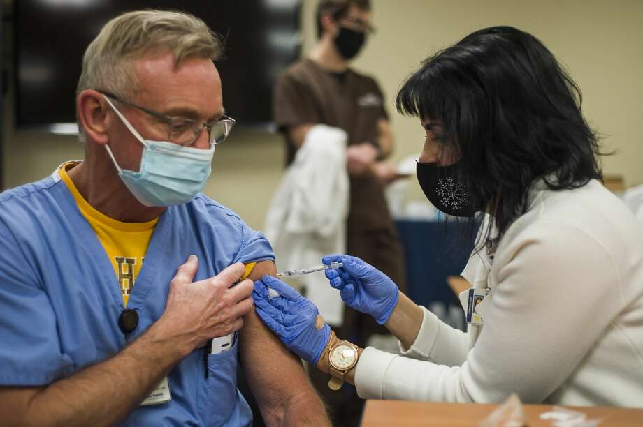 Colleen Markel, manager of workforce development for MidMichigan Medical Center-Midland, right, administers the Pfizer-BioNTech COVID-19 vaccine to Phil Tacey, left, during a vaccine clinic Wednesday, Jan. 6, 2021 at MidMichigan Medical Center-Midland. (Katy Kildee/kkildee@mdn.net) Photo: (Katy Kildee/kkildee@mdn.net)