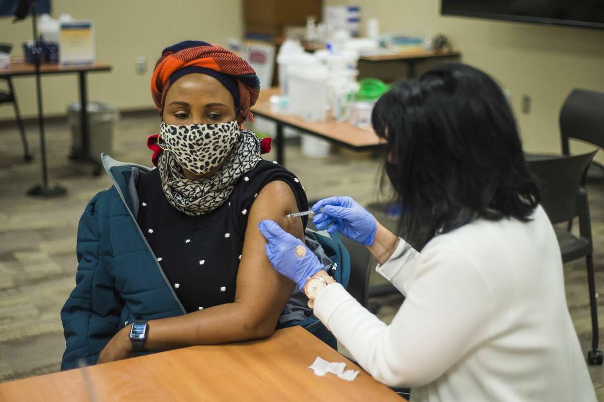 Colleen Markel, manager of workforce development for MidMichigan Medical Center-Midland, right, administers the Pfizer-BioNTech COVID-19 vaccine to Lucy Inungu, a medical assistant who works in Mt. Pleasant, left, during a vaccine clinic Wednesday, Jan. 6, 2021 at MidMichigan Medical Center-Midland. (Katy Kildee/kkildee@mdn.net)