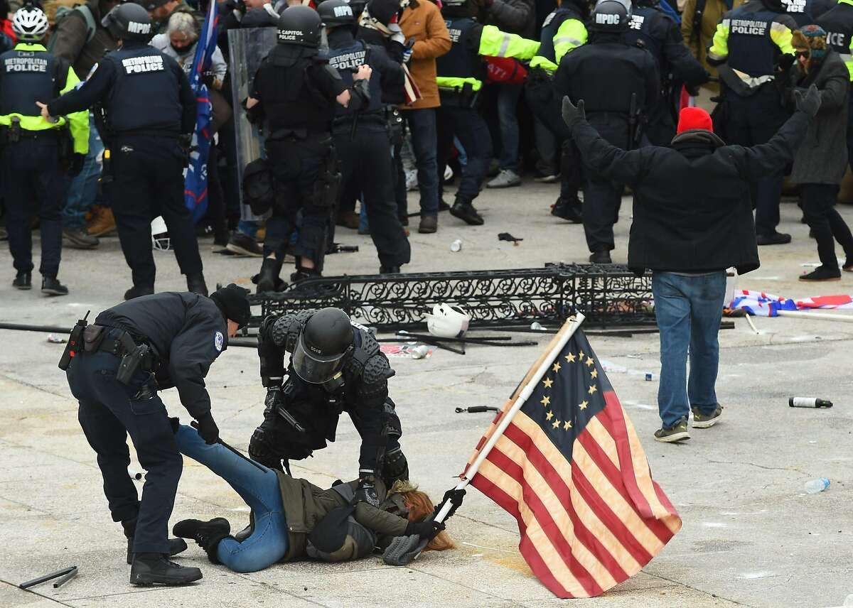 Police detain a President Donald Trump supporter outside the US Capitol on January 6, 2021, in Washington, DC.
