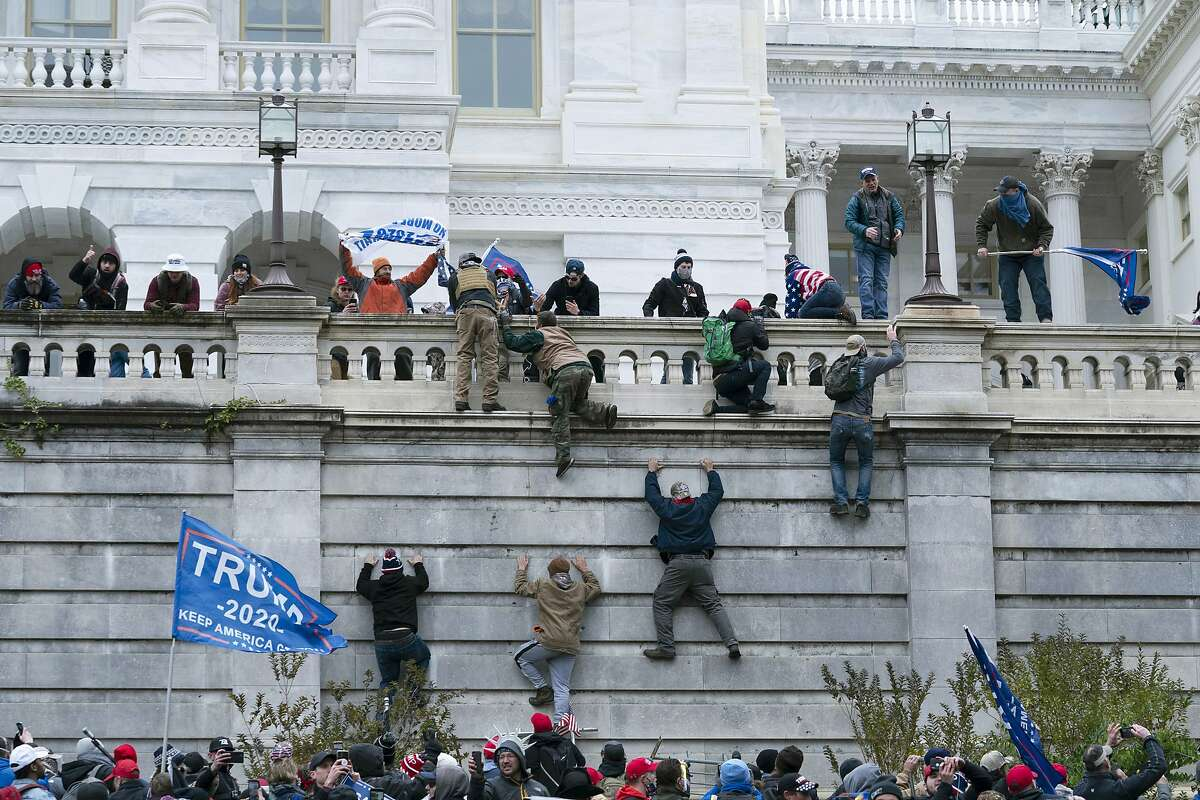 Supporters of President Donald Trump climb the west wall of the the U.S. Capitol on Jan. 6 in Washington.