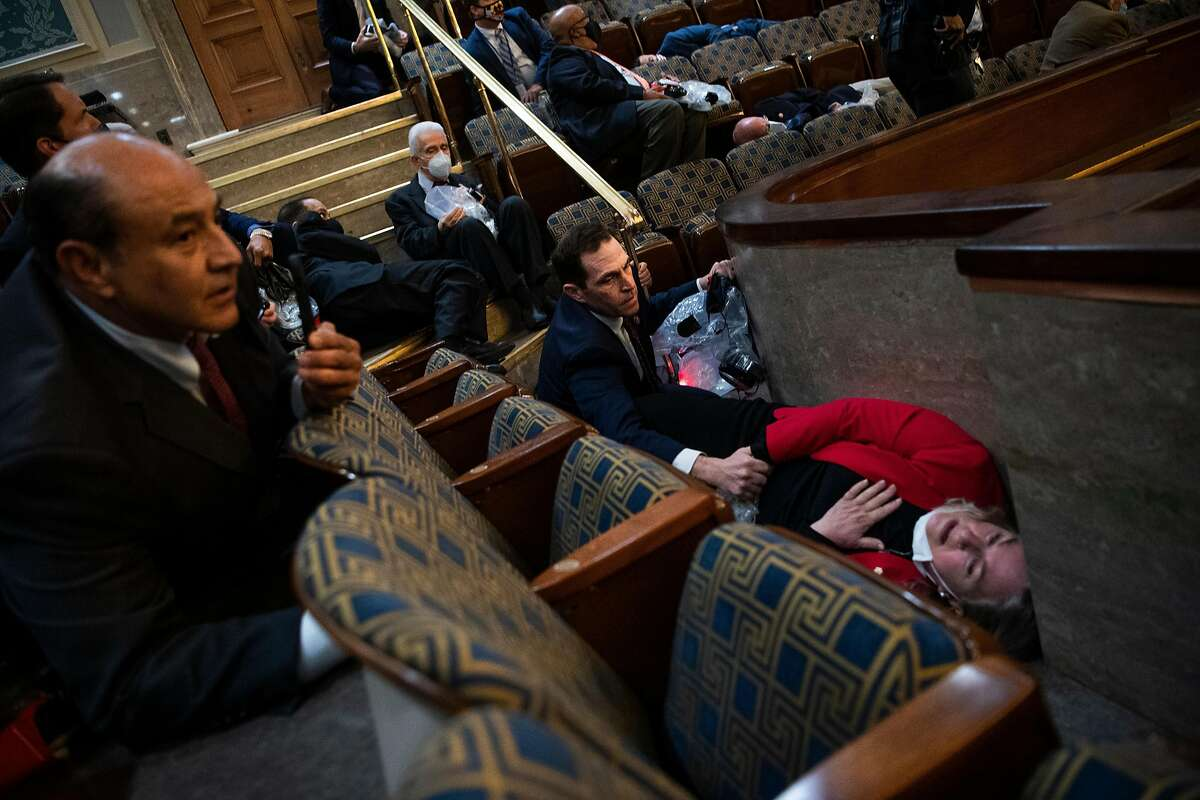 Rep. Jason Crow, D-Colo., comforts Rep. Susan Wild, D-Pa., while taking cover as Trump supporters disrupt the joint session of Congress to certify the Electoral College vote on Wednesday, January 6, 2021.