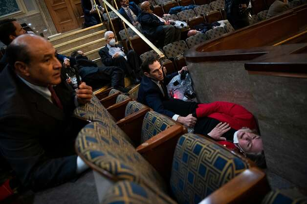 Rep. Jason Crow, D-Colo., comforts Rep. Susan Wild, D-Pa., while taking cover as Trump supporters disrupt the joint session of Congress to certify the Electoral College vote on Wednesday, January 6, 2021. Photo: Tom Williams, CQ-Roll Call, Inc Via Getty Images