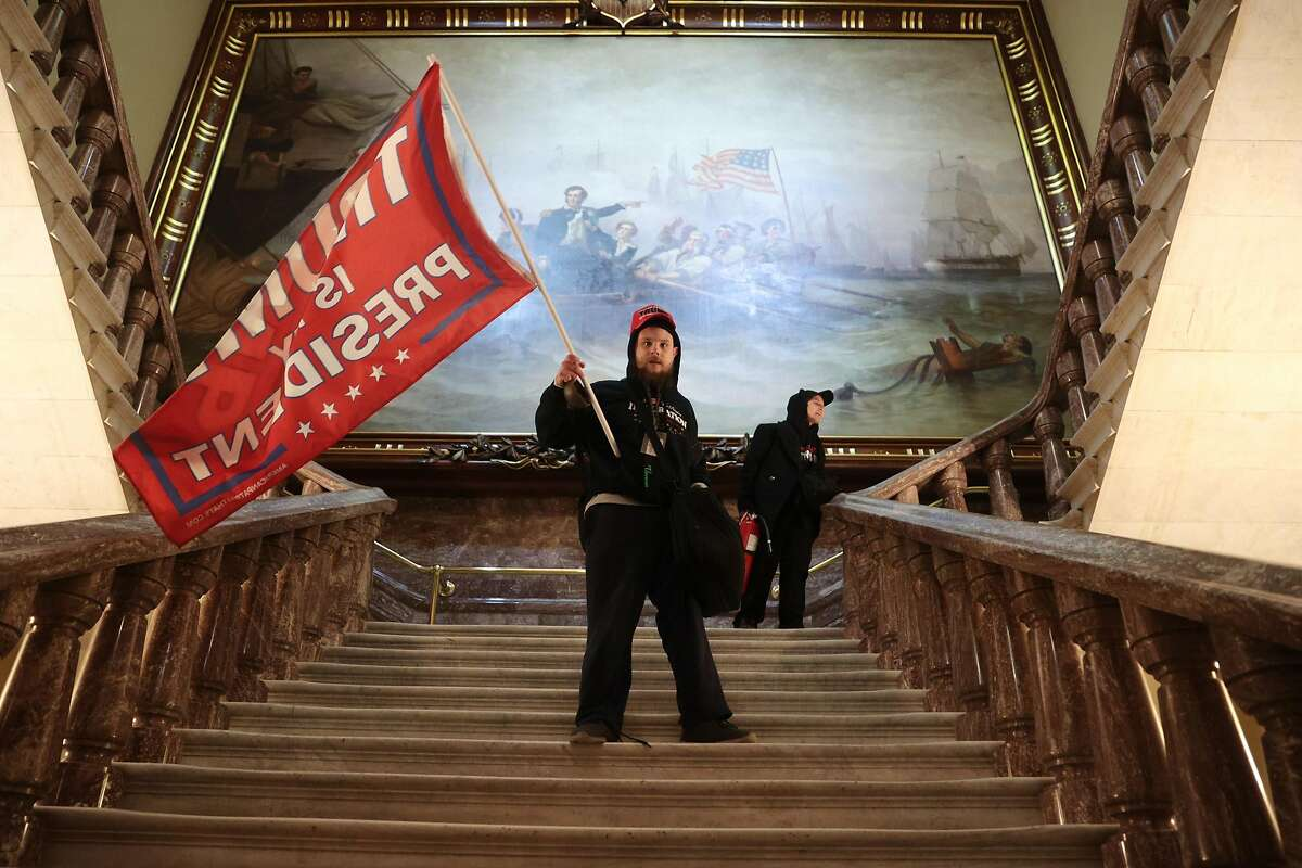 A man holds a Trump flag inside the U.S. Capitol near the Senate Chamber on Jan. 6, 2021, in Washington, D.C.