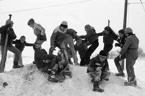 """On this day in 1981, the Manistee News Advocate front page featured Washington School sixth graders taking time out form the studies for an invigorating contest of """"king on the mountain."""" With the temperature in the low to mid-teens, the students had to do something to keep warm. (Manistee County Historical Museum photo)"""