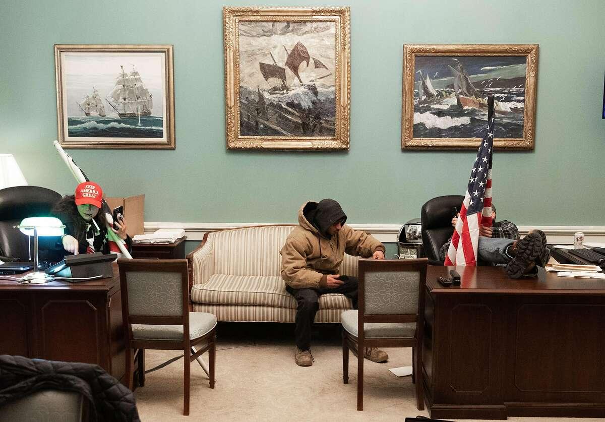 Pro-Donald Trump rioters sit in Nancy Pelosi's office in the U.S. Capitol on Jan. 6.