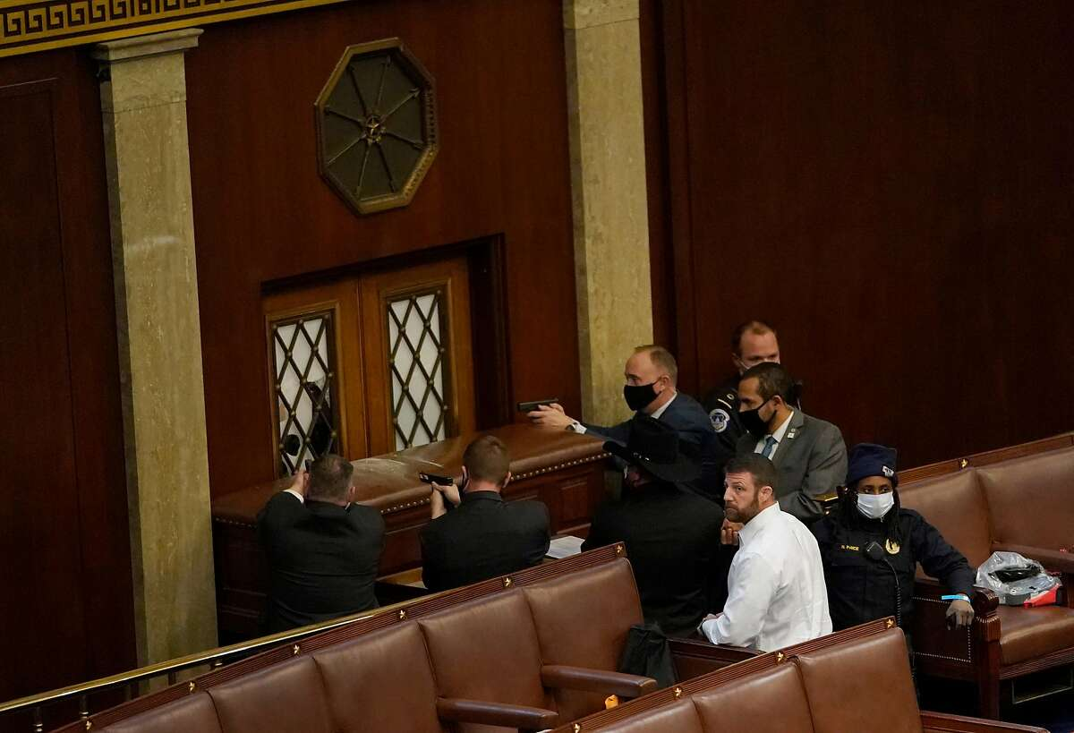 U.S. Capitol police officers point their guns at a door that was vandalized by Trump supporters in the House Chamber during a joint session of Congress on Jan. 6, 2021 in Washington, DC.
