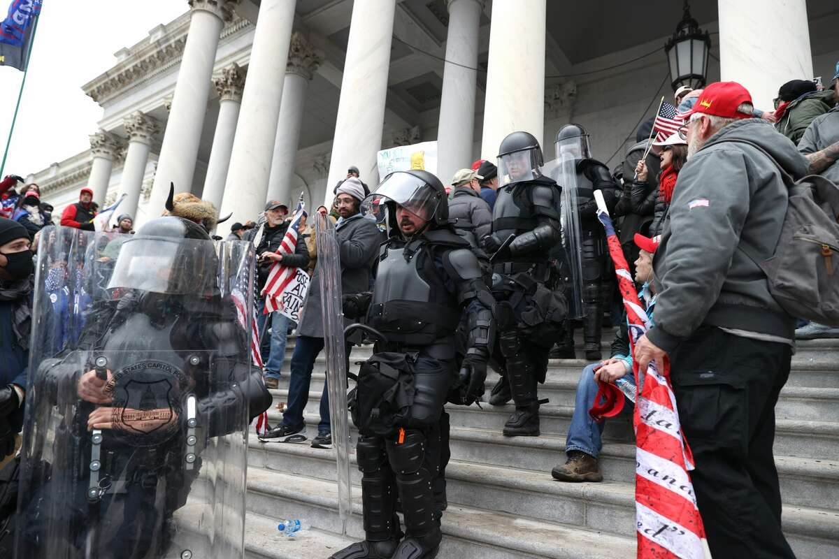 WASHINGTON, DC - JANUARY 06: Capitol police officers in riot gear walk through protesters that are gathered on the U.S. Capitol Building on January 06, 2021 in Washington, DC. Pro-Trump protesters entered the U.S. Capitol building after mass demonstrations in the nation's capital during a joint session Congress to ratify President-elect Joe Biden's 306-232 Electoral College win over President Donald Trump. (Photo by Tasos Katopodis/Getty Images)