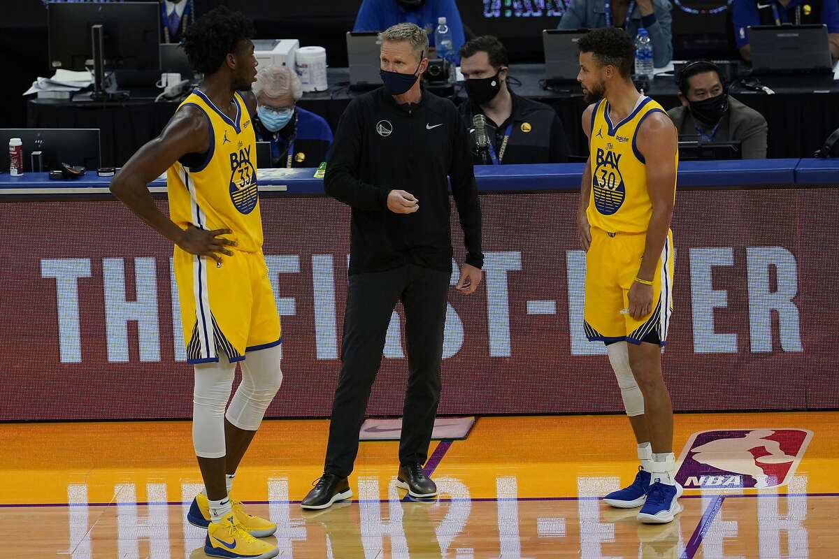 Golden State Warriors head coach Steve Kerr, center, talks with James Wiseman, left, and Stephen Curry against the Sacramento Kings during an NBA basketball game in San Francisco, Monday, Jan. 4, 2021. (AP Photo/Jeff Chiu)