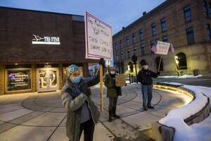 LoLita Pfeiffer, left, holds a sign as a small group of people gather outside the Midland office of U.S. Rep. John Moolenaar Wednesday, Jan. 6, 2021 to protest his support of the president after a pro-Trump mob breached the U.S. Capitol in Washington D.C. hours earlier. (Katy Kildee/kkildee@mdn.net)