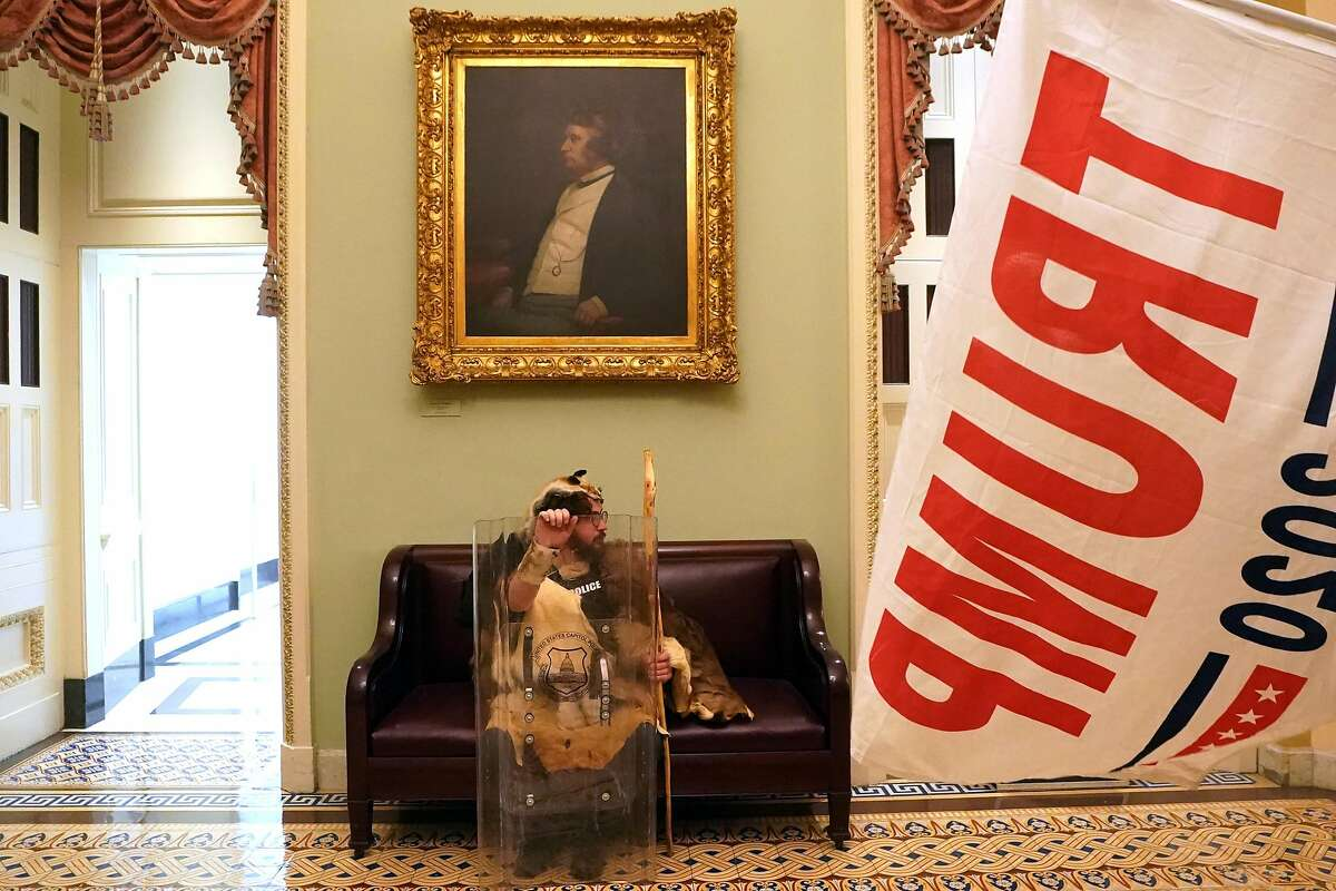 A Trump supporter with a tactical shield sits in a hallway of the Capitol in Washington on Wednesday, Jan. 6, 2020, after they breached security and entered the building.