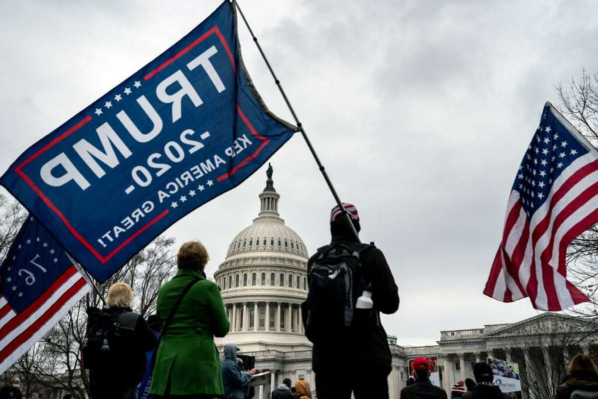 Supporters of Pesident Donald Trump wave flags as they protest the result of the presidential election in front of the Capitol in Washington on Tuesday, Jan. 5, 2020. A joint session of Congress is scheduled for Wednesday to certify the Electoral College vote count.