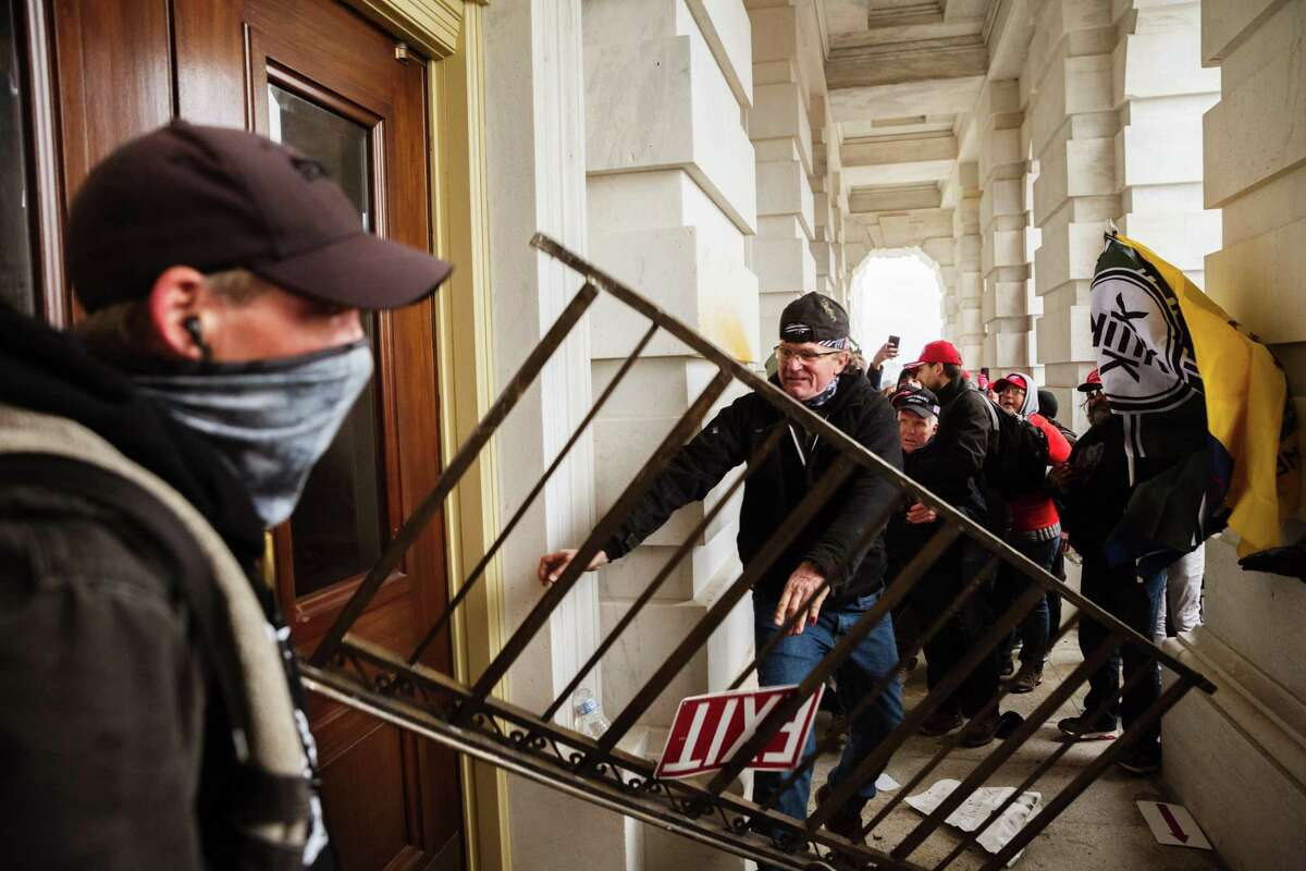 A person bashes an entrance of the Capitol Building in an attempt to gain access on Jan. 6, 2021. in Washington, D.C.