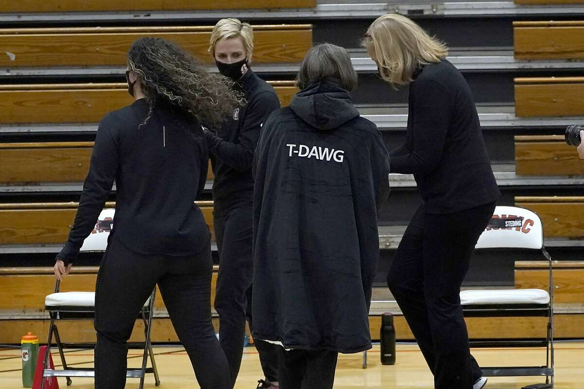 """Stanford coach Tara VanDerveer, center, wears an overcoat with """"T-DAWG"""" on the back that was given to her from her team after Stanford's 104-61 win over Pacific in an NCAA college basketball game made her the winningest coach in women's basketball history, Tuesday, Dec. 15, 2020, in Stockton, Calif. VanDerveer passed the late Pat Summitt with her 1,099th victory."""