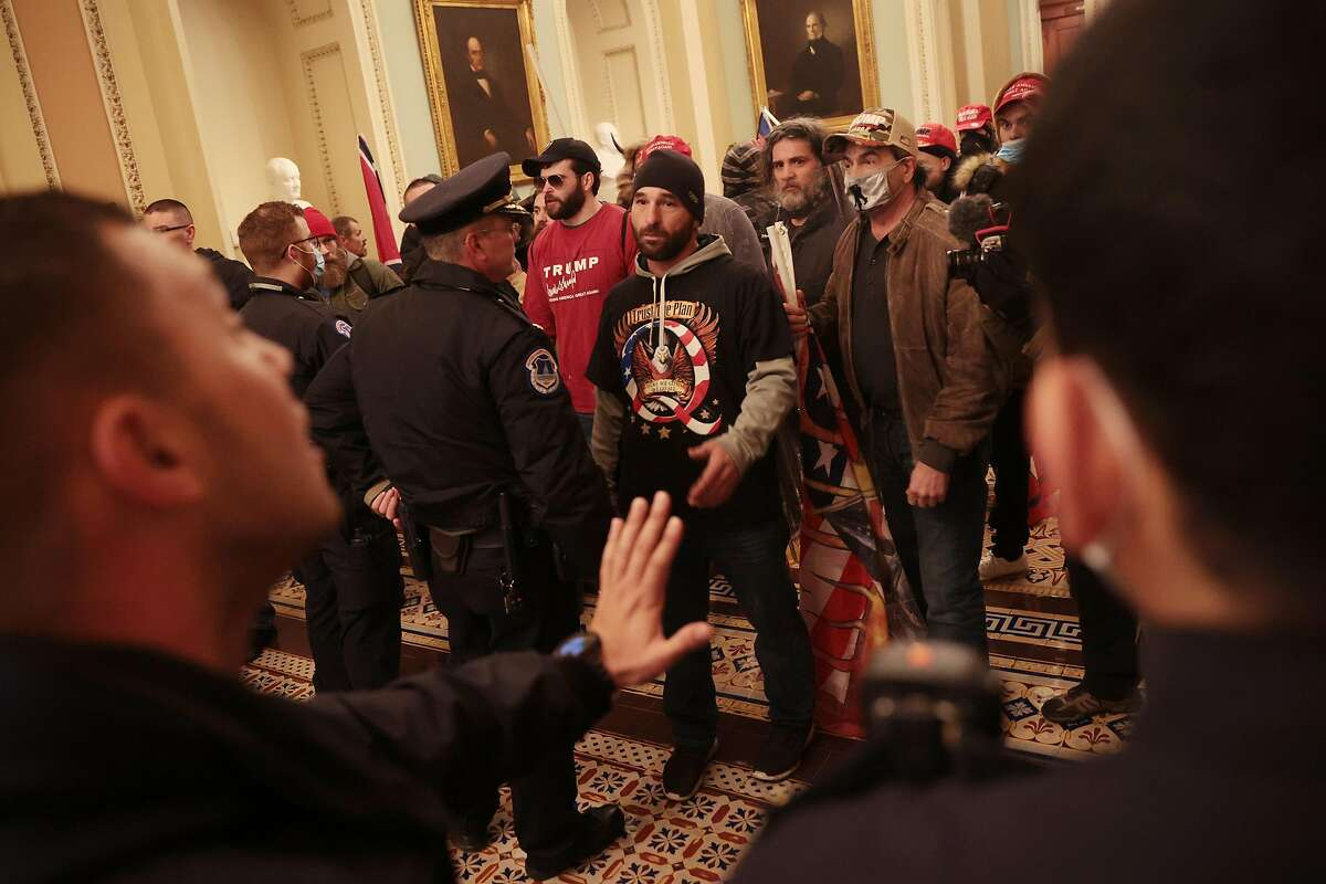 """Rioters interact with police inside the U.S. Capitol on Wednesday. Black Lives Matter tweeted that the """"coup by hundreds of pro-Trump supporters is one more example of the hypocrisy in our country's law enforcement response to protest."""""""