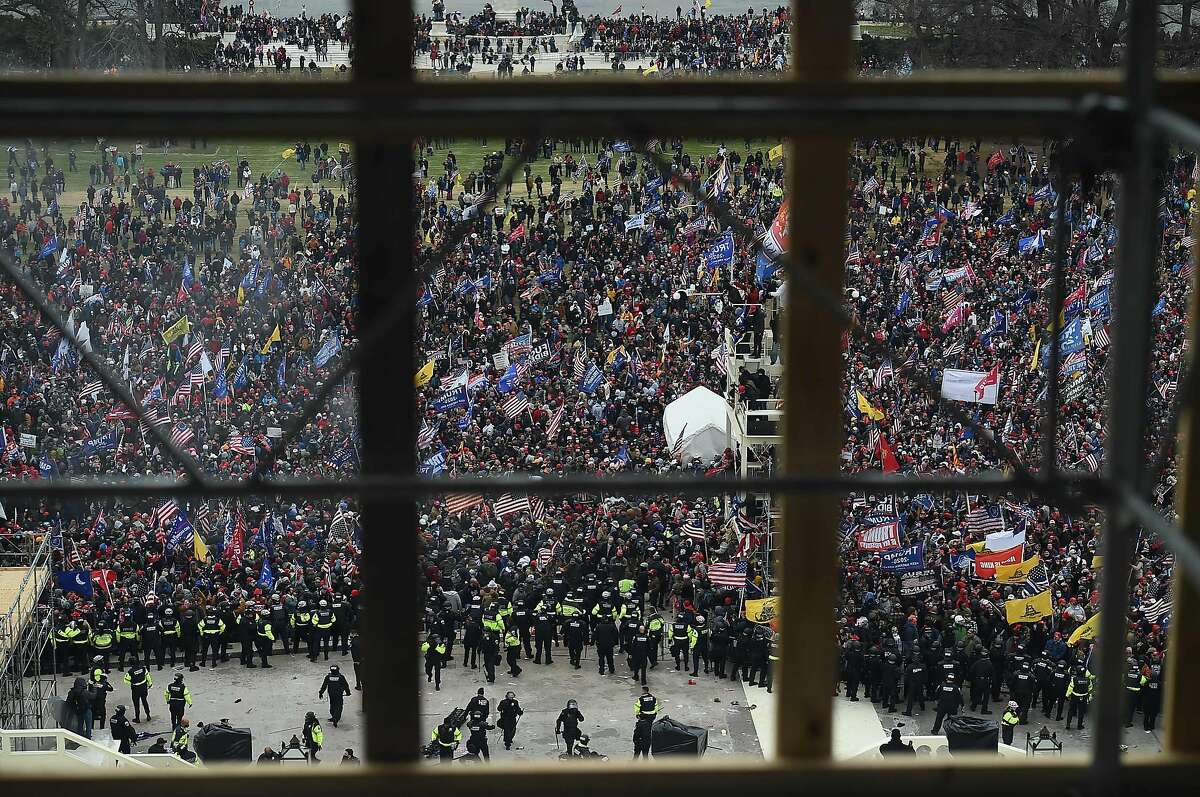Police hold back supporters of US President Donald Trump as they gather outside the US Capitol's Rotunda on January 6, 2021, in Washington, DC. - Demonstrators breeched security and entered the Capitol as Congress debated the a 2020 presidential election Electoral Vote Certification. (Photo by Olivier DOULIERY / AFP) (Photo by OLIVIER DOULIERY/AFP via Getty Images)