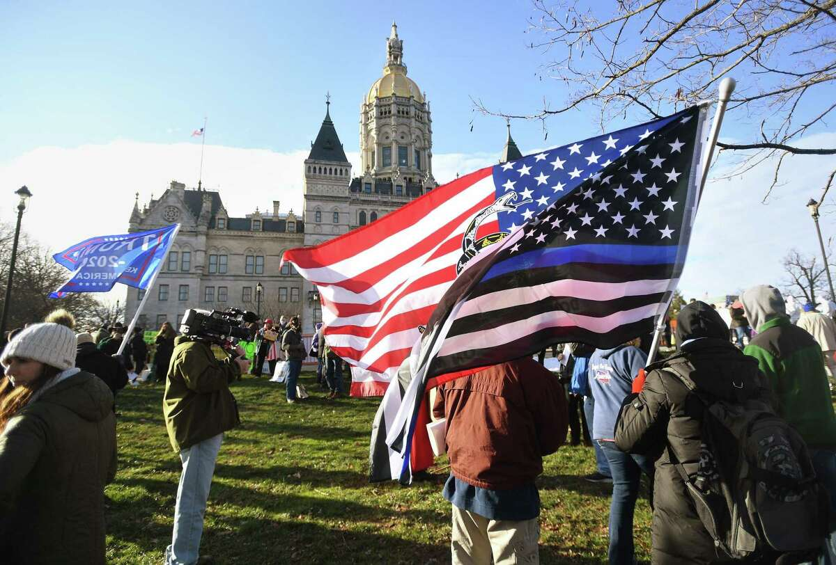 Protestors gather outside the swearing in ceremonies and opening session of the legislature at the Capitol in Hartford, Conn. on Wednesday, January 6, 2021.