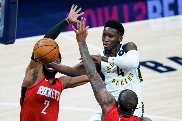 Indiana Pacers guard Victor Oladipo (4) shoots over Houston Rockets center DeMarcus Cousins (15) and guard David Nwaba (2) during the first quarter of an NBA basketball game in Indianapolis, Wednesday, Jan. 6, 2021. (AP Photo/Michael Conroy) Photo: Michael Conroy, Associated Press / Copyright 2021 The Associated Press. All rights reserved.