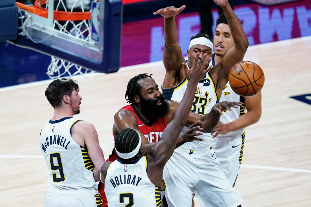 Houston Rockets guard James Harden (13) passes between Indiana Pacers forward Myles Turner (33) and guard Aaron Holiday (3) during the third quarter of an NBA basketball game in Indianapolis, Wednesday, Jan. 6, 2021. (AP Photo/Michael Conroy)