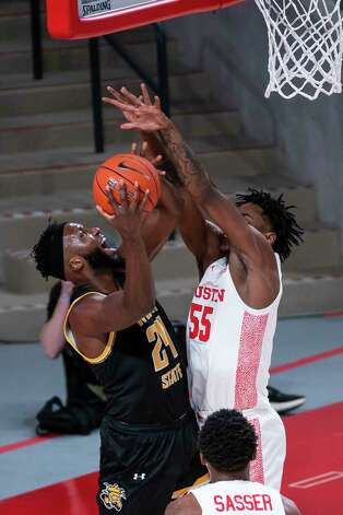 Houston Cougars forward Brison Gresham (55) tries to stop a shot by Wichita State Shockers forward Morris Udeze (24) during the first half of a game between the University of Houston Cougars and the Wichita State Shockers on Wednesday, Jan. 6, 2021, at the Feritta Center in Houston. Photo: Mark Mulligan, Staff Photographer / © 2021 Mark Mulligan / Houston Chronicle
