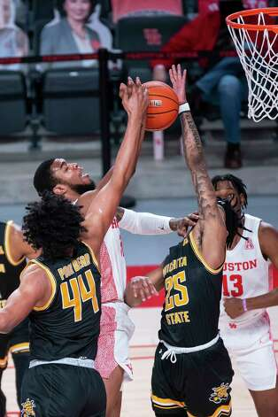Houston Cougars forward Justin Gorham (4) tries to grab a rebound from Wichita State Shockers forward Isaiah Poor Bear-Chandler (44) and forward Clarence Jackson (25) during the first half of a game between the University of Houston Cougars and the Wichita State Shockers on Wednesday, Jan. 6, 2021, at the Feritta Center in Houston. Photo: Mark Mulligan, Staff Photographer / © 2021 Mark Mulligan / Houston Chronicle