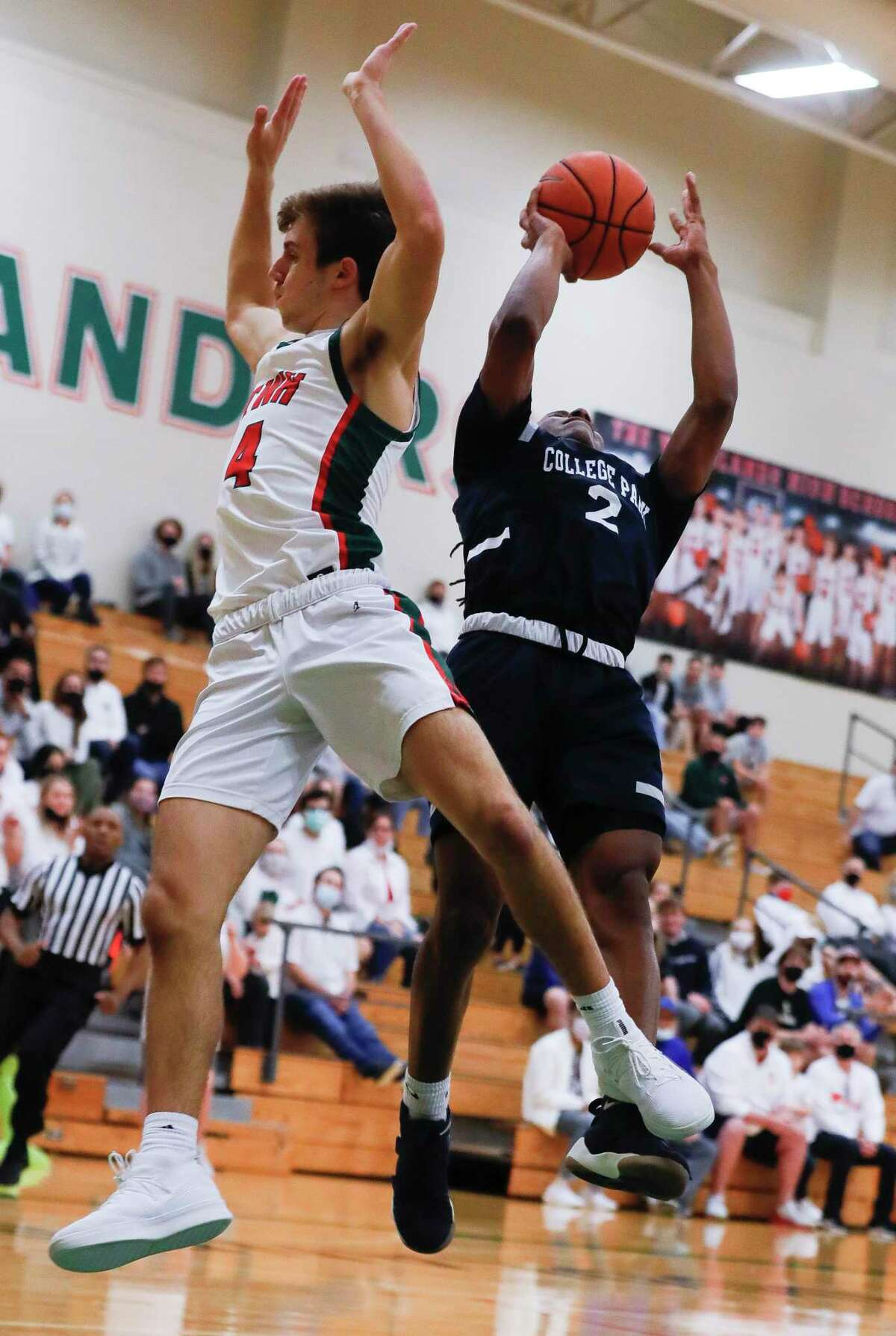 College Park guard Marvin Dock (2) shoots past The Woodlands guard Cade Moore (4) during the first quarter of a District 13-6A high school basketball game at The Woodlands High School, Wednesday, Jan. 6, 2021, in The Woodlands.