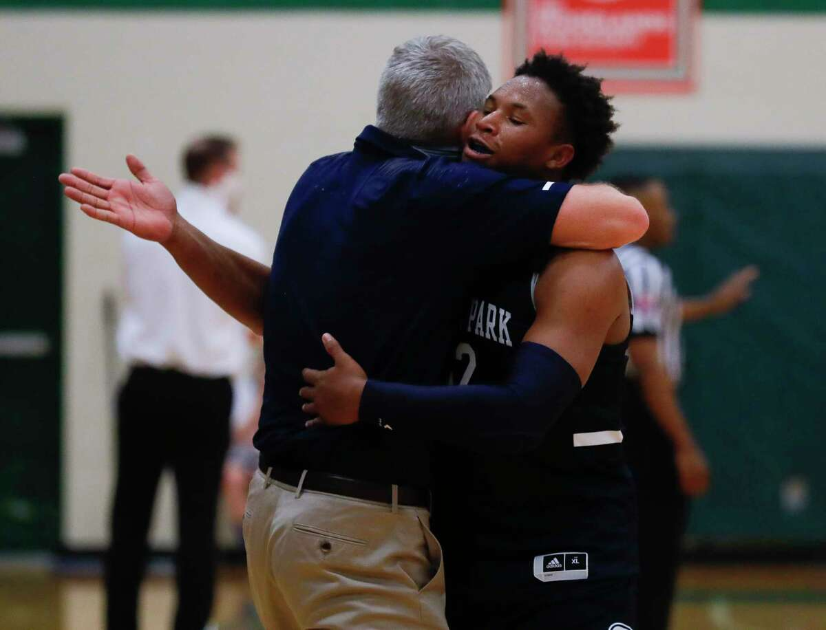 College Park guard Drew Calderon (3) gets a hug from head coach Clifton McNeely during the fourth quarter of a District 13-6A high school basketball game at The Woodlands High School, Wednesday, Jan. 6, 2021, in The Woodlands.