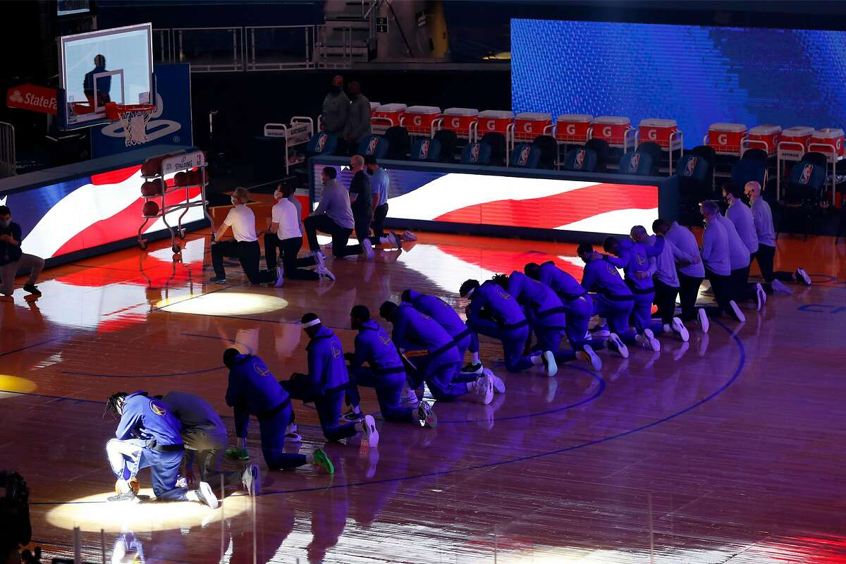 Members of the Warriors kneel during the national anthem before playing Clippers at Chase Center after a day that saw a mob storm the U.S. Capitol building.