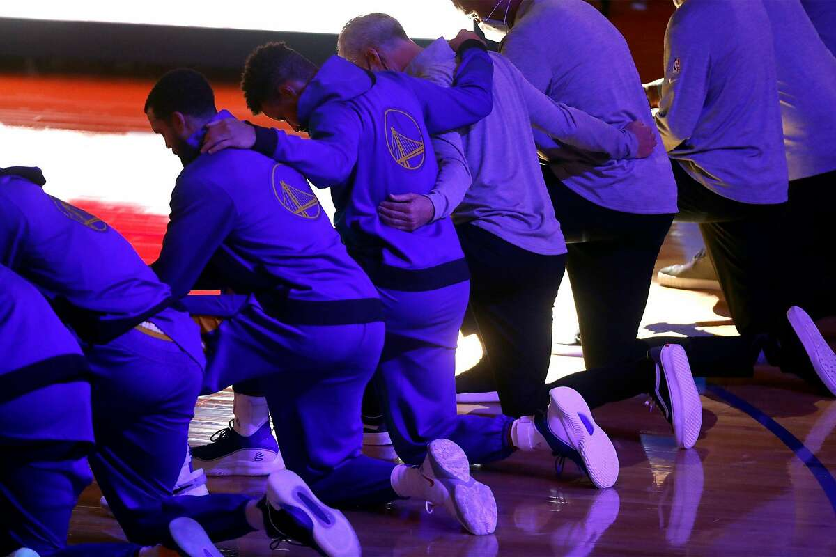 Golden State Warriors' Stephen Curry joins teammates and coaching staff in kneeling during National Anthem before playing Los Angeles Clippers during NBA game at Chase Center in San Francisco, Calif., on Wednesday, January 6, 2021.