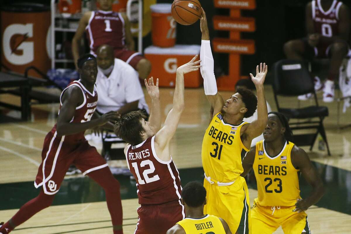 Baylor guard MaCio Teague (31) is called for the foul as he gets a hand on the shot of Oklahoma guard Austin Reaves (12) during the second half of an NCAA college basketball game on Wednesday, Jan. 6, 2021, in Waco, Texas. (AP Photo/Ray Carlin)