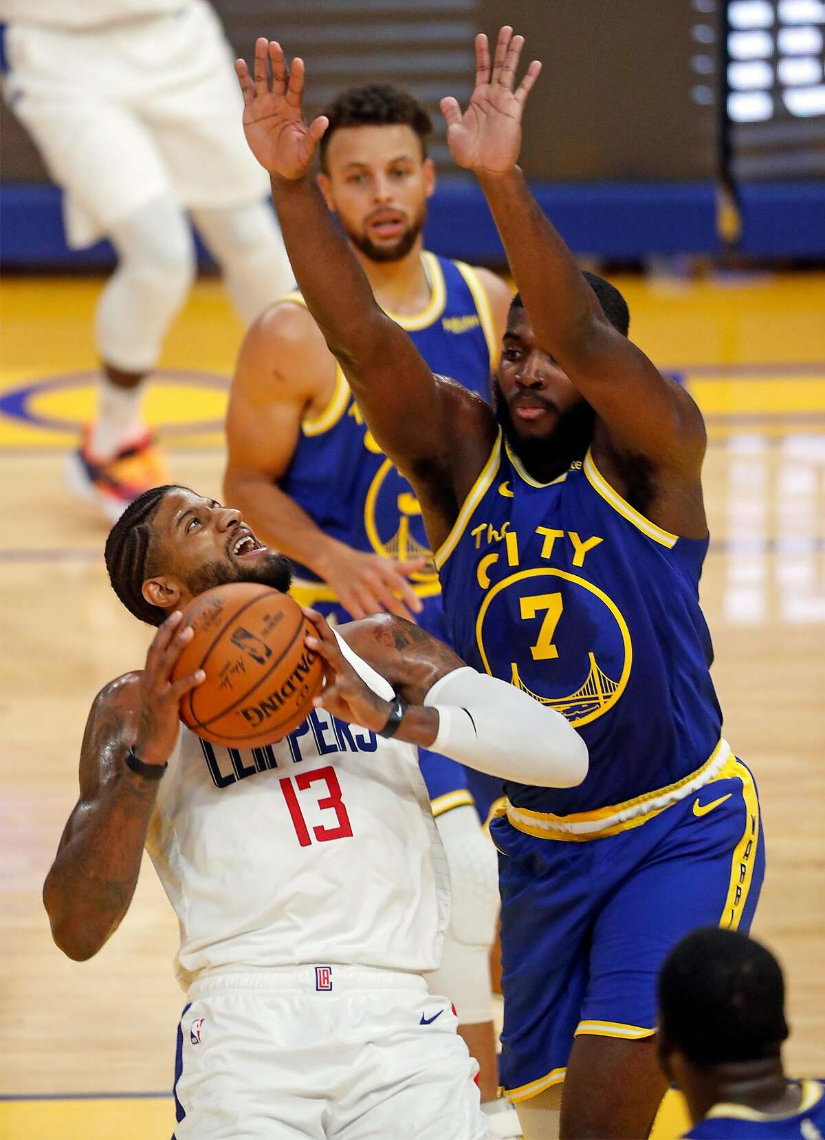 Golden State Warriors' Eric Paschall guards Los Angeles Clippers' Paul George in 2nd quarter during NBA game at Chase Center in San Francisco, Calif., on Wednesday, January 6, 2021.