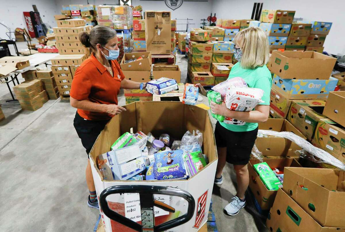 Volunteer Suzanne Hollifield, left, helps June Kolesar sort through child items for a client at Saint Isidore Episcopal Church's event space, Thursday, July 16, 2020, in Spring. The non-profit fed up to 800 families a week last year from its food pantry.