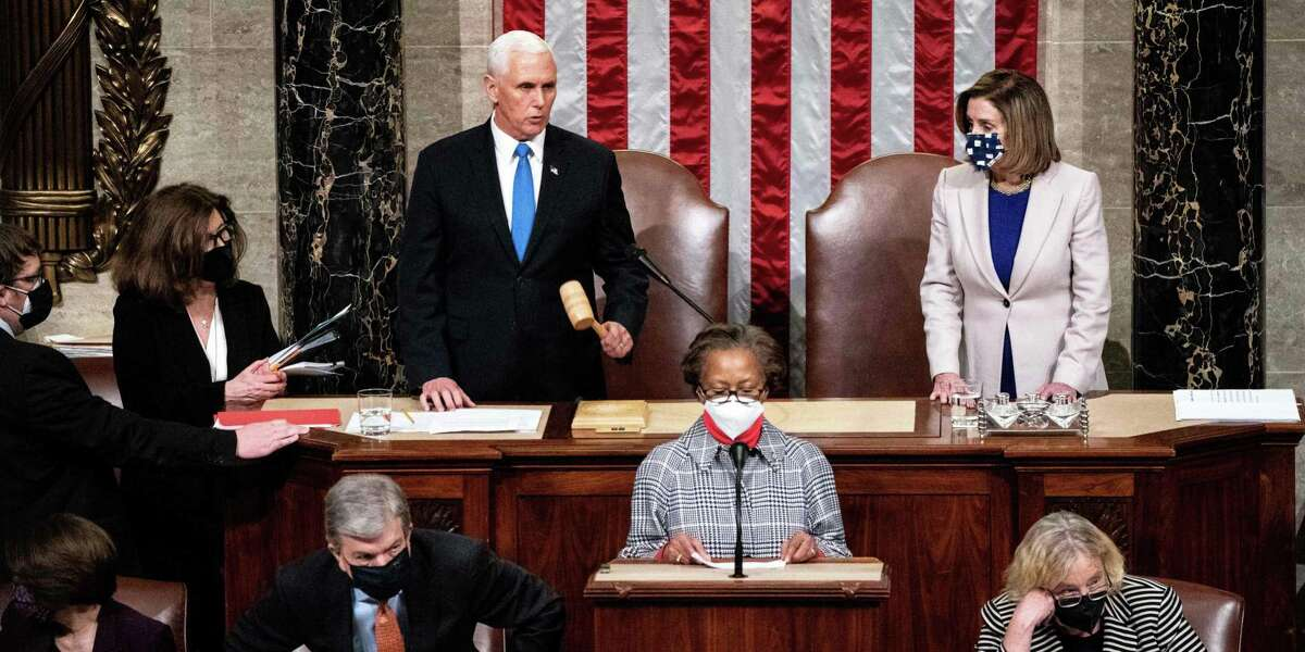TOPSHOT - Vice President Mike Pence and House Speaker Nancy Pelosi preside over a Joint session of Congress to certify the 2020 Electoral College results after supporters of President Donald Trump stormed the Capitol earlier in the day on Capitol Hill in Washington, DC on January 6, 2020. - Members of Congress returned to the House Chamber after being evacuated when protesters stormed the Capitol and disrupted a joint session to ratify President-elect Joe Biden's 306-232 Electoral College win over President Donald Trump. (Photo by Erin Schaff / POOL / AFP) (Photo by ERIN SCHAFF/POOL/AFP via Getty Images)