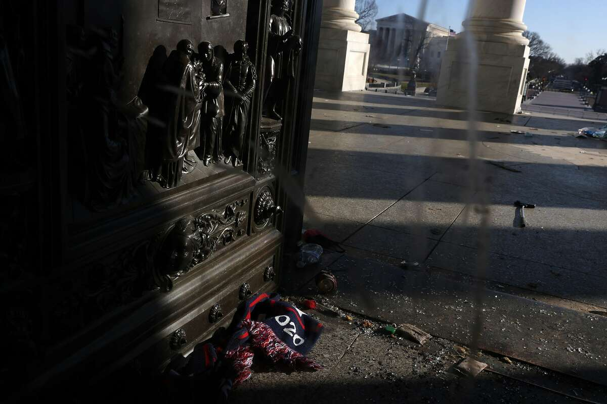 A scarf is left behind outside a damaged entrance of the U.S. Capitol January 7, 2021 in Washington, DC. The U.S. Congress has finished the certification for President-elect Joe Biden and Vice President-elect Kamala Harris' electoral college win after pro-Trump mobs stormed the Capitol and temporarily stopped the process.