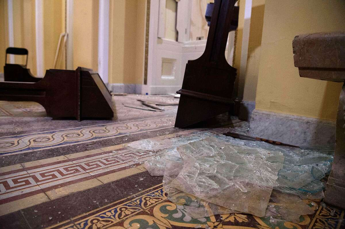 Overturned furniture and broken glass litter a hallway of the US Capitol in Washington, DC, on January 7, 2021, one day after supporters of outgoing President Donald Trump stormed the building.